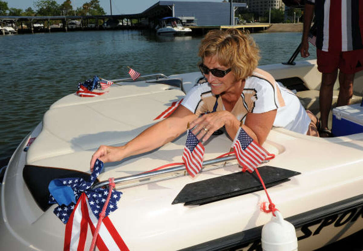 Nancy Pittman fixes the flag on her boat for American Spirit Boat Parade out of the Nassau Bay Yacht Club. This event was a benefit for the Military Order of Purple Heart Chapter 723.