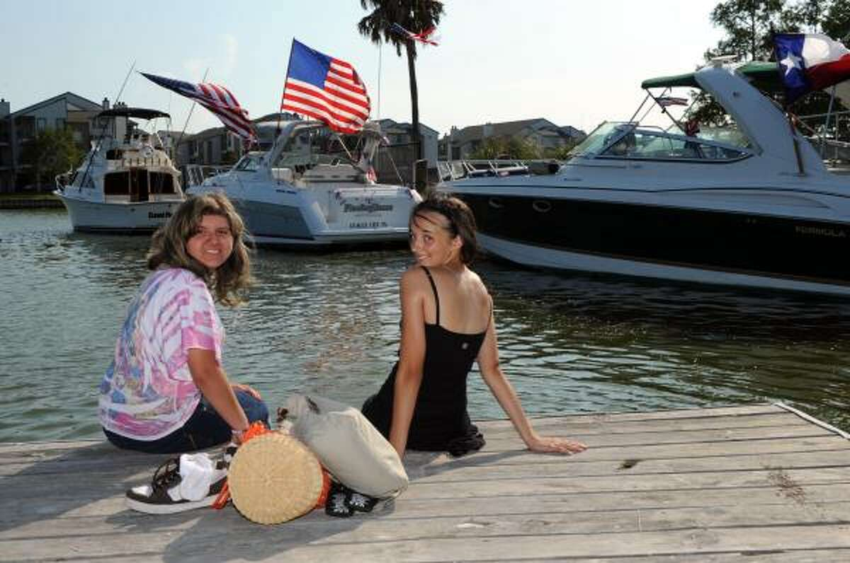 Hannah Klingbeil and Sabina Fesler sit on the end of the dock at the yacht club.