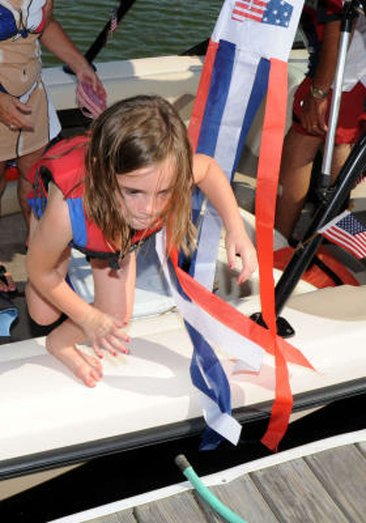 Cadence Tilton, 6, jumps out of the boat after the parade.