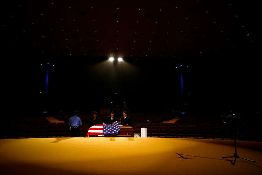 A police officer stands guard as attendants prepare the casket of HPD Senior Police Officer Henry Canales, 42, during funeral services for the fallen officer at Grace Community Church. Photo: Michael Paulsen, Chronicle