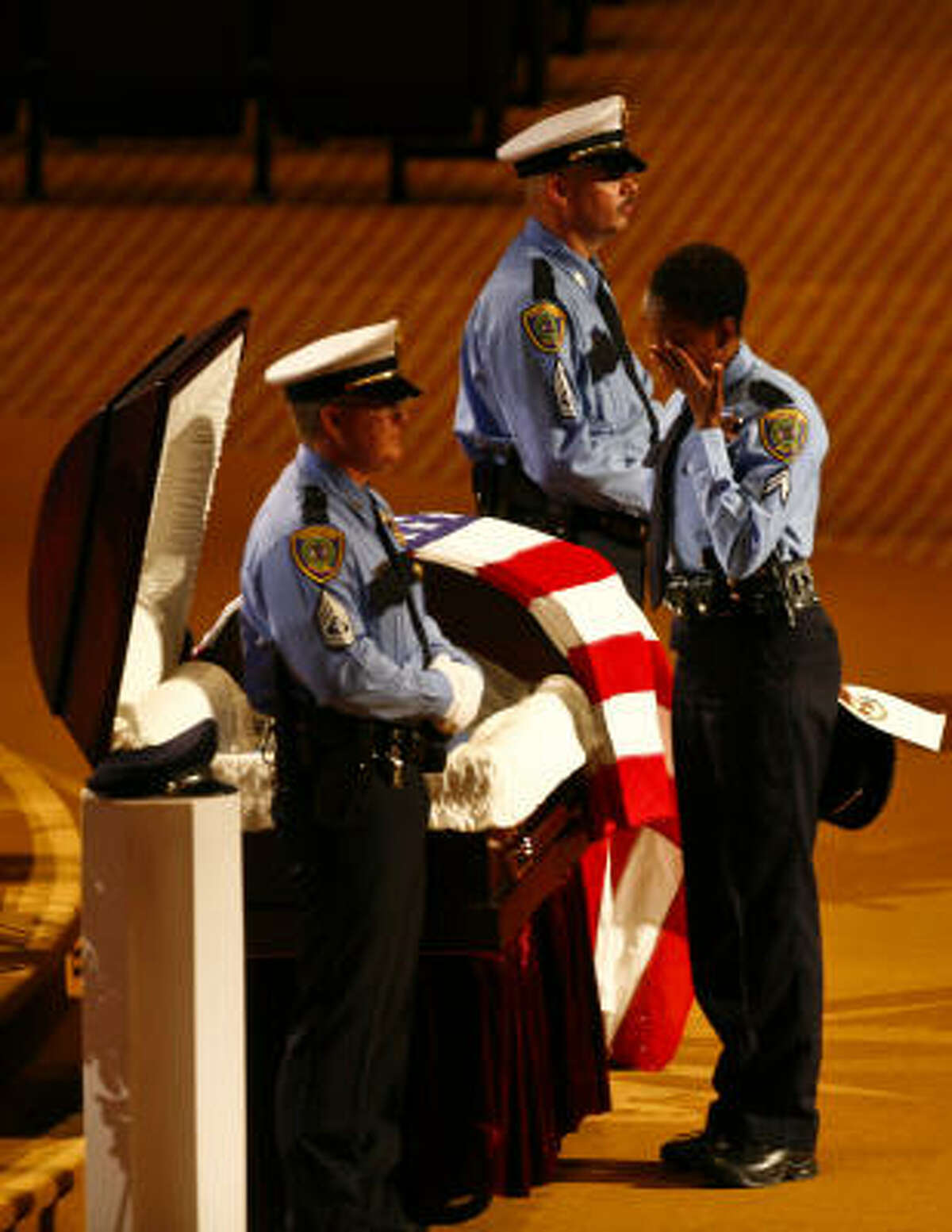 Police officer, Krystal Charles pays respect before the casket of HPD Senior Police Officer Henry Canales, 42, at Grace Community Church where funeral services for the fallen officer were held in Houston.