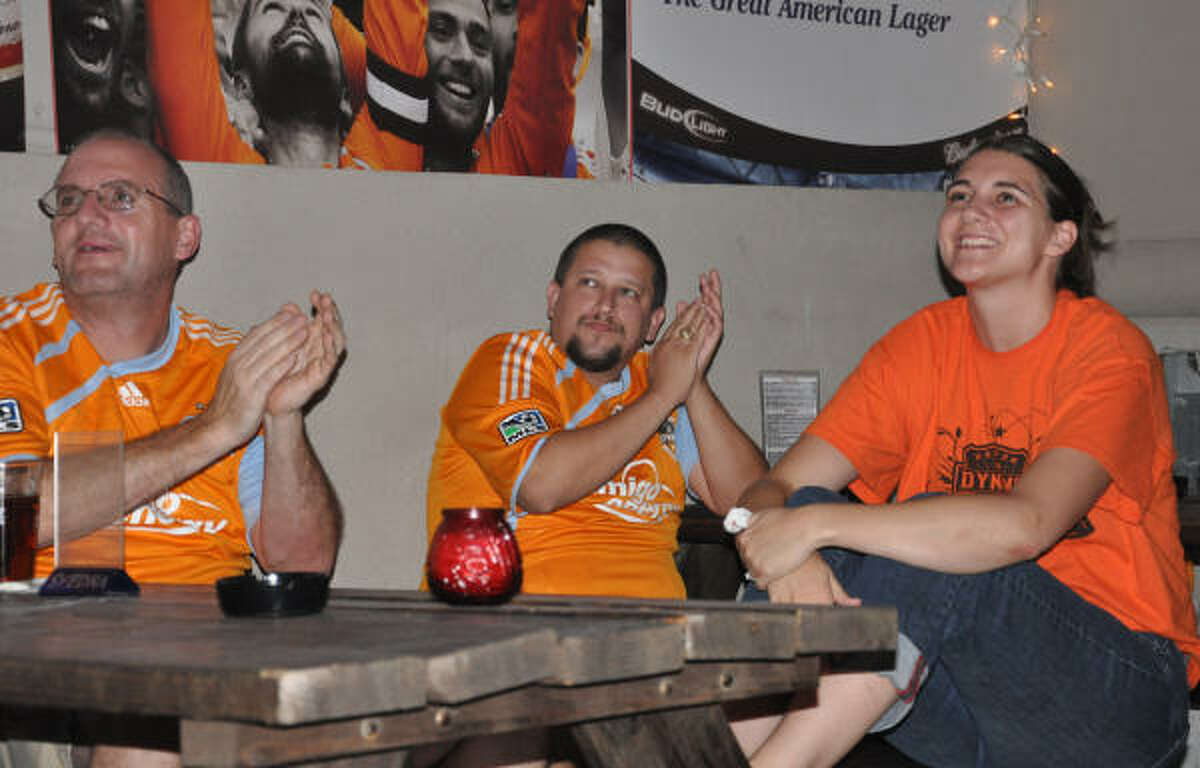 Andy Jackson, left, Rene Korzarsky, middle, and Meghan Stapleton applaud a shot-on-goal that is deflected by the Dynamo.