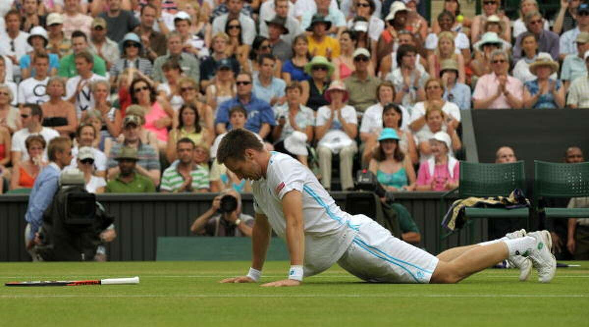 Sweden's Robin Soderling picks himself up after a fall as he plays against Switzerland's Roger Federer.