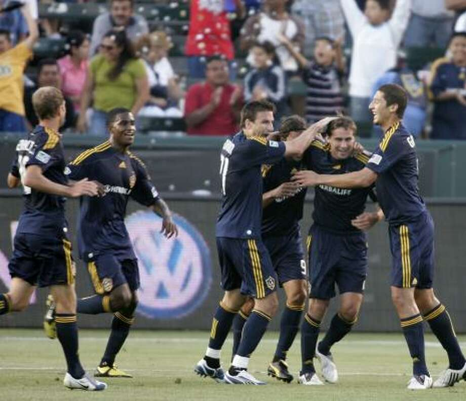 Los Angeles Galaxy teammates congratulate Todd Dunivant, second from right, after he scored the only goal of the game against the Dynamo. Photo: Branimir Kvartuc, AP