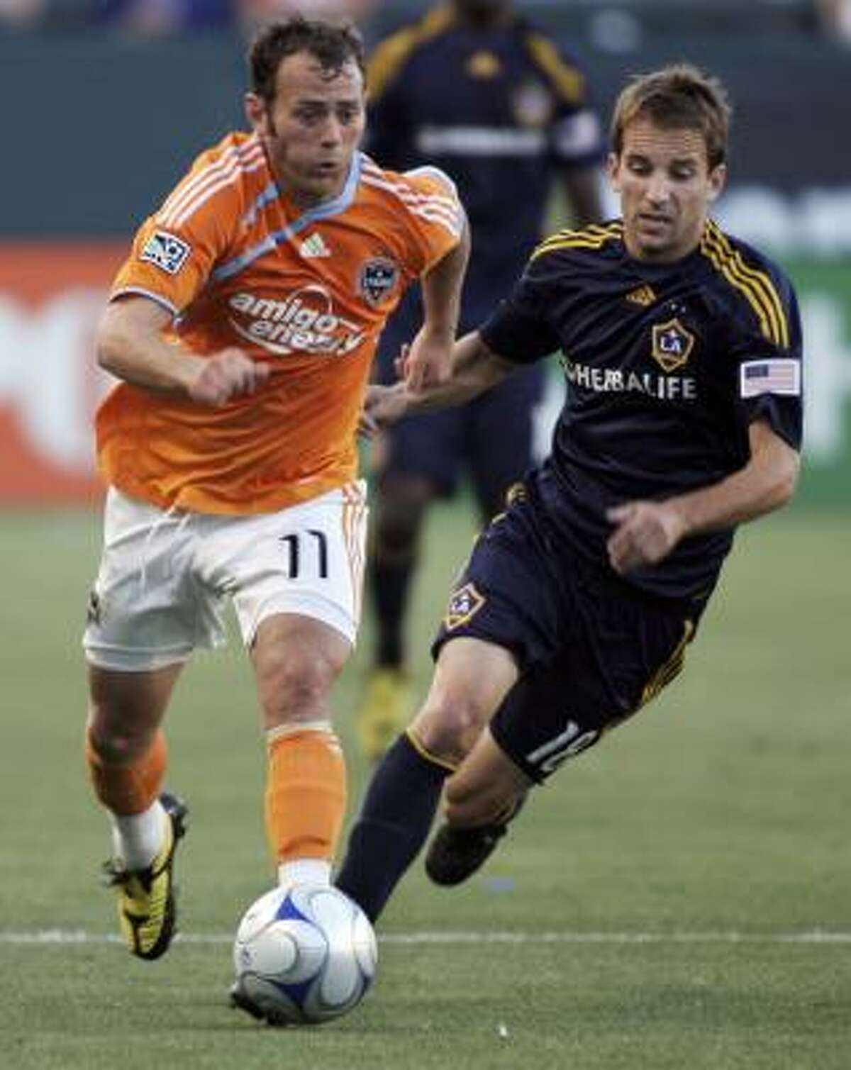 The Dynamo's Brad Davis, left, dribbles the ball in front of Los Angeles' Mike Magee.