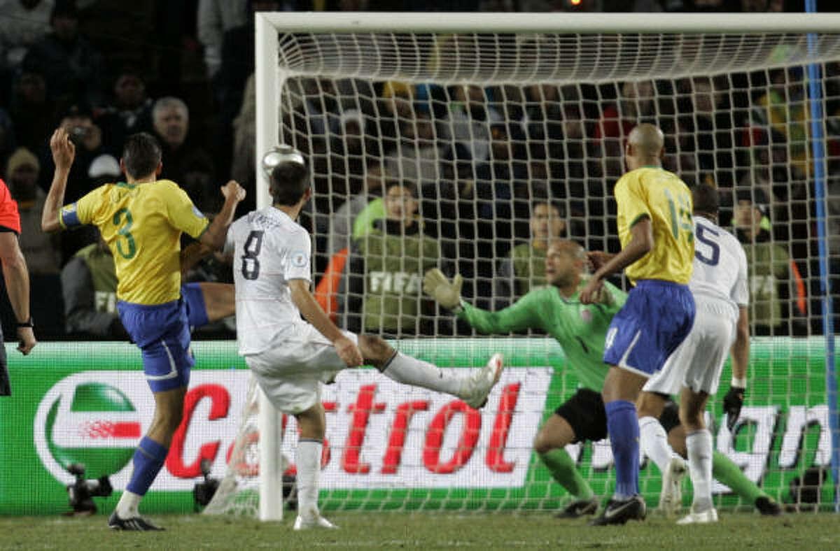 Brazil's Lucio, left, kicks the eventual game-winning goal past U.S. goalkeeper Tim Howard.