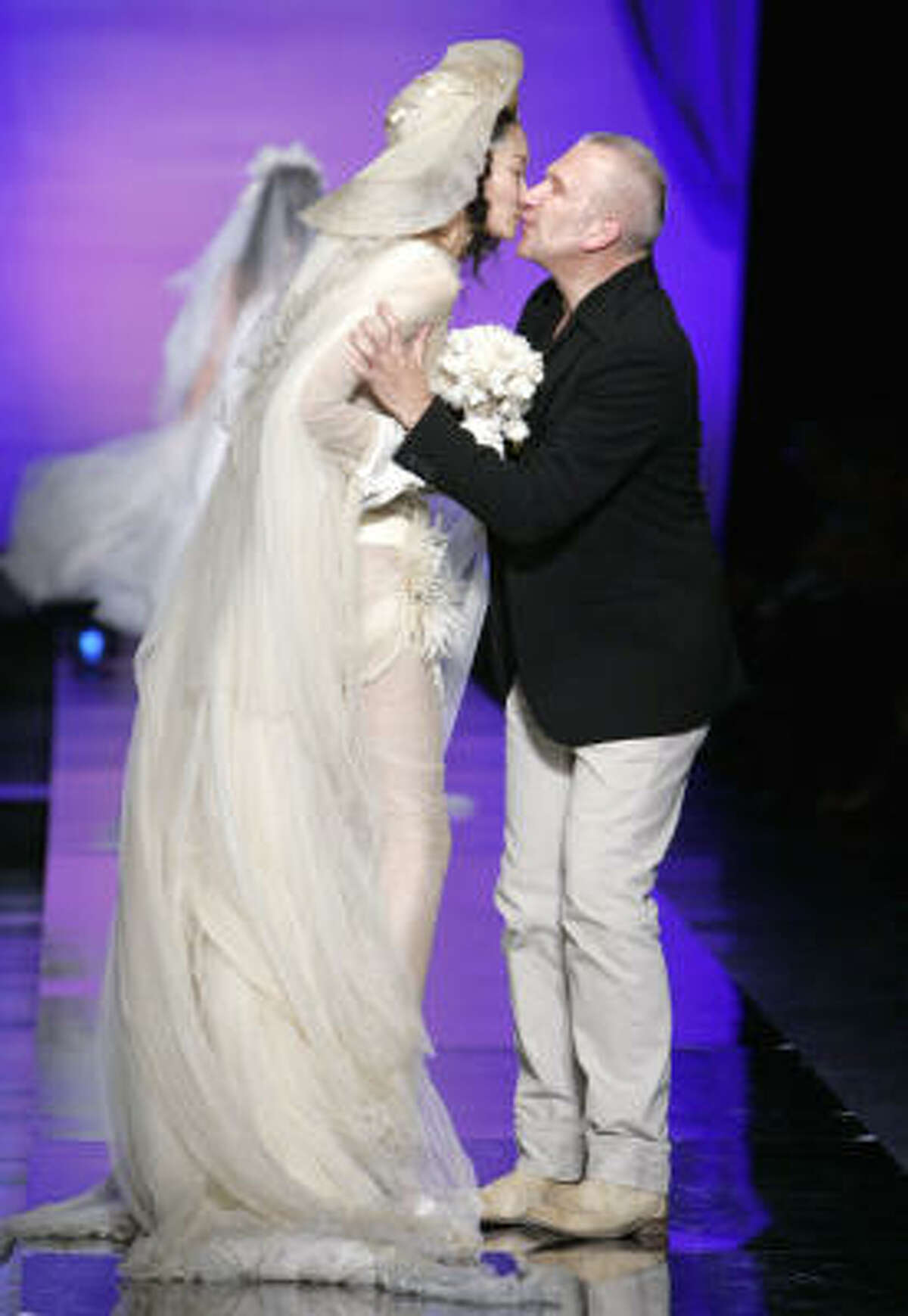 French fashion designer Jean-Paul Gaultier kisses a model in a wedding dress.