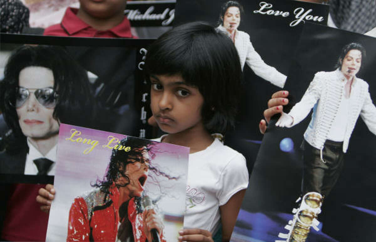Even in India, Jackson's music impacted a younger generation. A girl holds a photo of him in Bangalore.