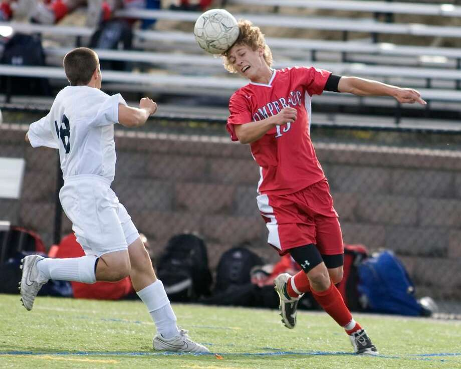 Pomperaug's Kyle Molnar heads the ball away from Adam Cannale of New Fairfield during an SWC soccer match Thursday at New Fairfield High. Photo: Barry Horn / The News-Times