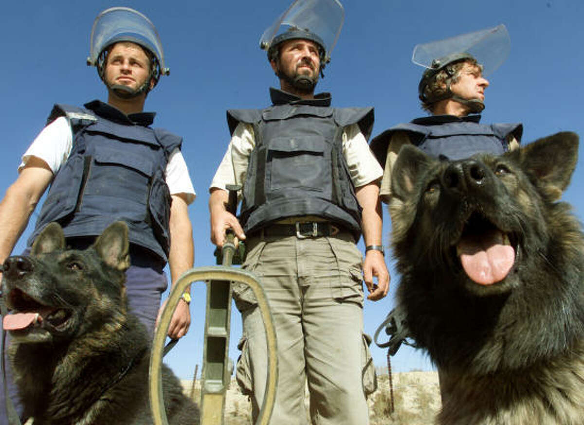 Bosnian deminers with dogs Sarik and Brenda pose for photos at U.S. Air Base Bagram, north of Kabul, Afghanistan.