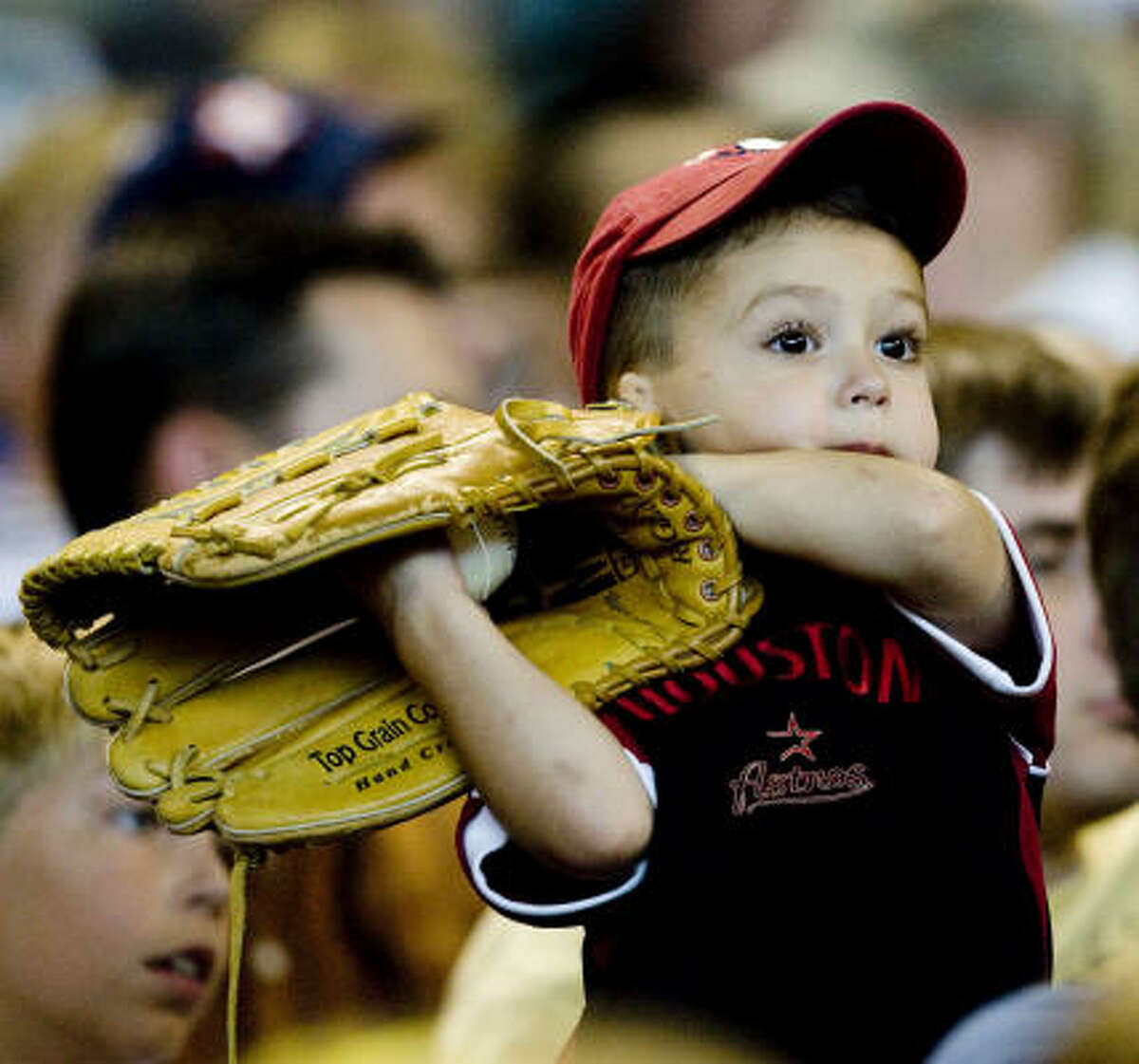 Astros fan Cade Powell, 2, holds a baseball glove during Thursday's series finale against the Royals.