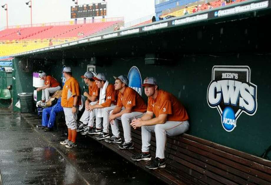 Game 2: Texas 5, LSU 1From left to right: Texas' Cameron Rupp (3), Cole Green (24) and Austin Wood (44) sit in the dugout during a rain delay before facing elimination against LSU. Photo: Elsa, Getty Images