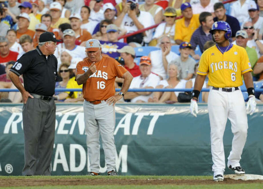 Texas coach Augie Garrido, center, argues with first-base umpire Steve Manders over whether LSU's Leon Landry (6) was safe at first base in the second inning. Photo: Dave Weaver, AP