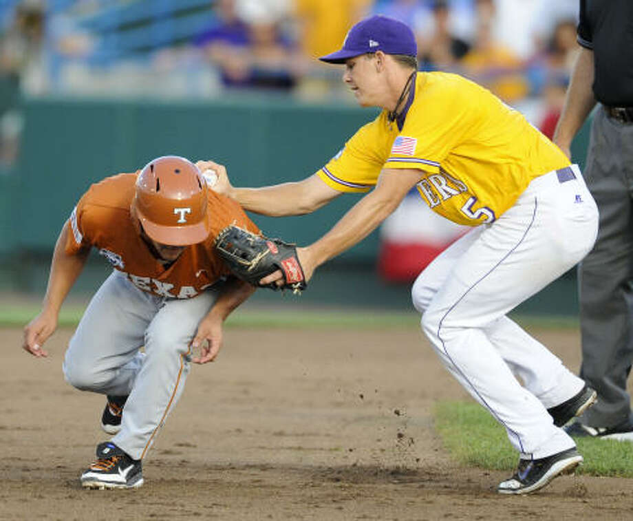 Texas' Michael Torres, left, is tagged out between second and third base by LSU third baseman Derek Helenihi in the second inning. Photo: Dave Weaver, AP