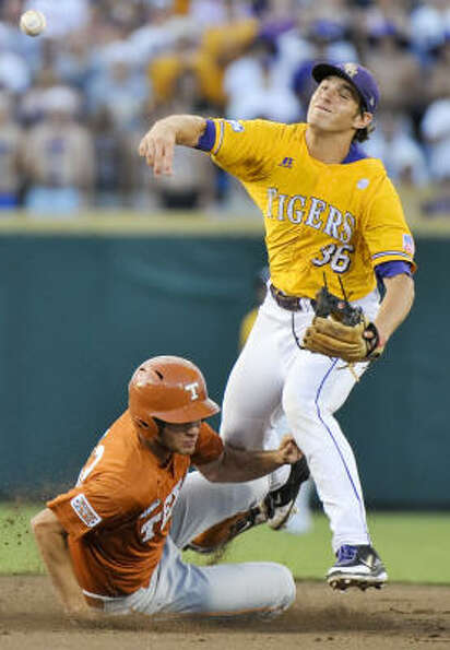 Texas' Brandon Belt is out at second base as LSU shortstop Austin Nola throws to first in the first