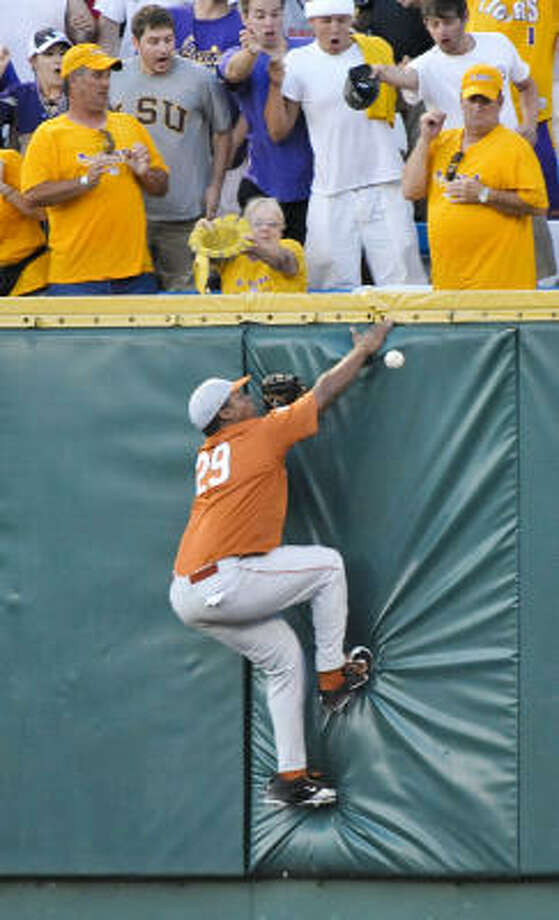 Texas right fielder Kevin Keyes climbs the wall trying to catch a triple off the bat of LSU's DJ LeMahieu in the third inning. Photo: Ted Kirk, AP