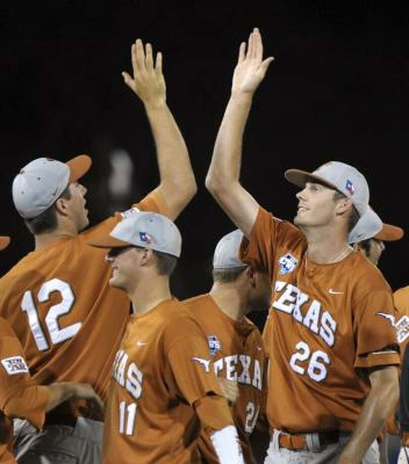 Texas's Taylor Jungmann, who pitched a complete game against LSU, high-fives pitcher Brandon Workman (12) at the end of Game 2. Photo: Ted Kirk, AP