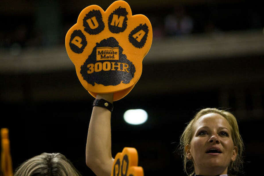Fans show off their puma paws, given away before a ceremony celebrating Lance Berkman's 300th career home run. Photo: Smiley N. Pool, Chronicle