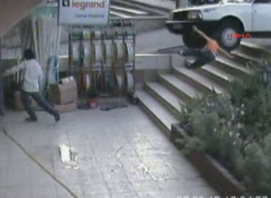 Muhammet Dirlik of Sanliufra, Turkey, had been standing on the pavement Saturday when a car went out of control in a shopping area. Here's the first in a sequence of photos from a security camera. Photo: AP
