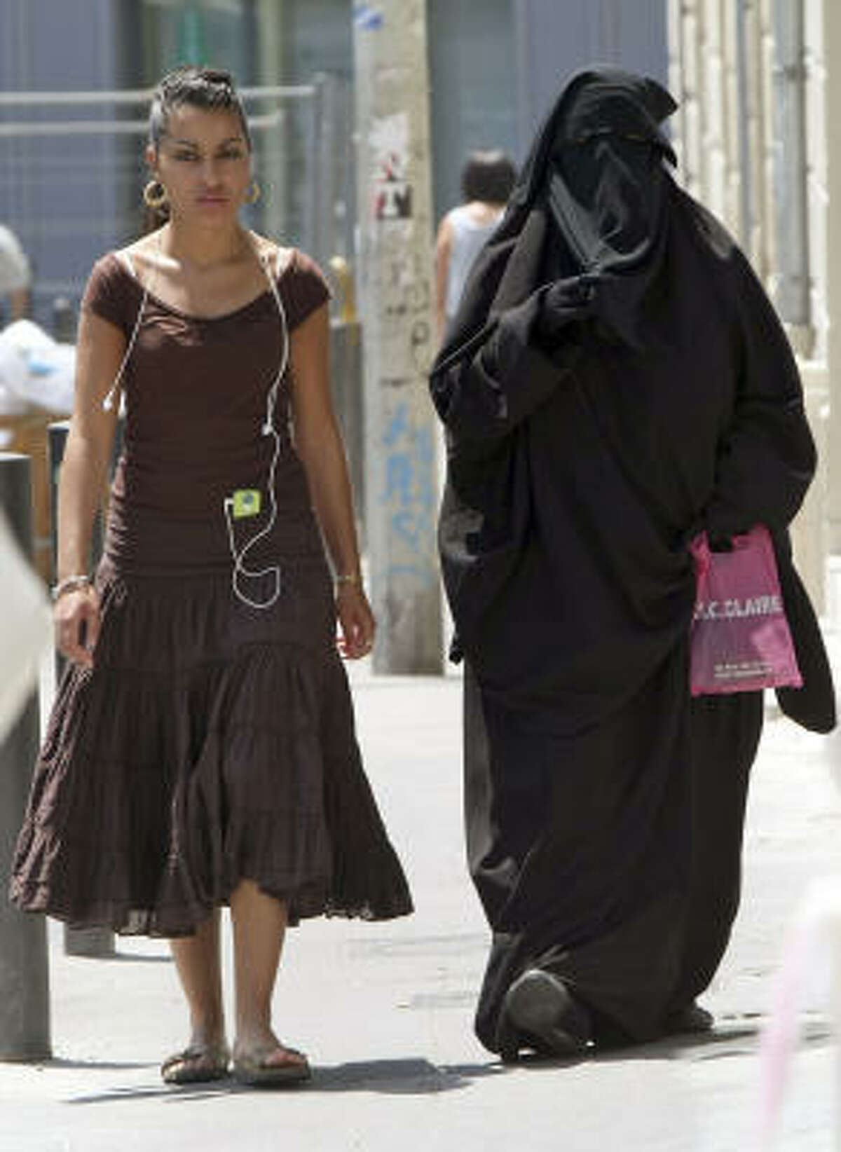 Two women, one wearing the niqab, a veil worn by the most conservative Muslims that exposes only a woman's eyes, right, walk side by side, in the Belsunce district of downtown Marseille, central France, Friday June 19, 2009. The French government's spokesman says he favors the creation of a parliamentary commission to study the small but growing trend of burqa wear in France. Luc Chatel says the commission could possibly propose legislation aimed at banning the burqa and other fully covering garments worn by some Muslim women.