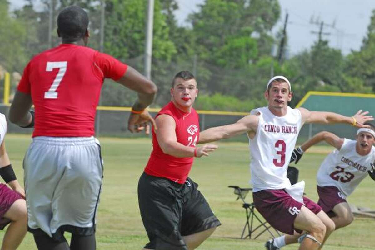 Atascocita quarterback Chazz Carrington, No. 7, throws to Cody Nicholson, No. 24, with Cinco Ranch players defending.