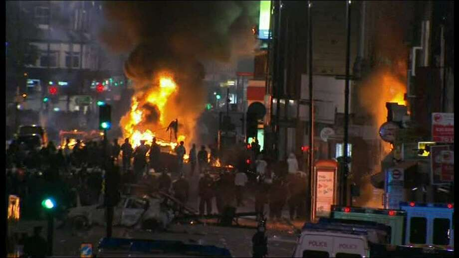 "In this image from video, a bus and shop burn in  Tottenham, north London late Saturday Aug 6 2011 after two police cars were attacked by members of a community where a young man was shot dead by police on Thursday, took to the streets to demand ""justice"".  Officers had been attempting to carry out an arrest under the Trident operational command unit, which deals with gun crime in the black community, according to the Independent Police Complaints Commission  (AP Photo/Sky tv via APTN ) UNITED KINGDOM OUT  NO SALES   TV OUT Photo: TEL / SKY TV"