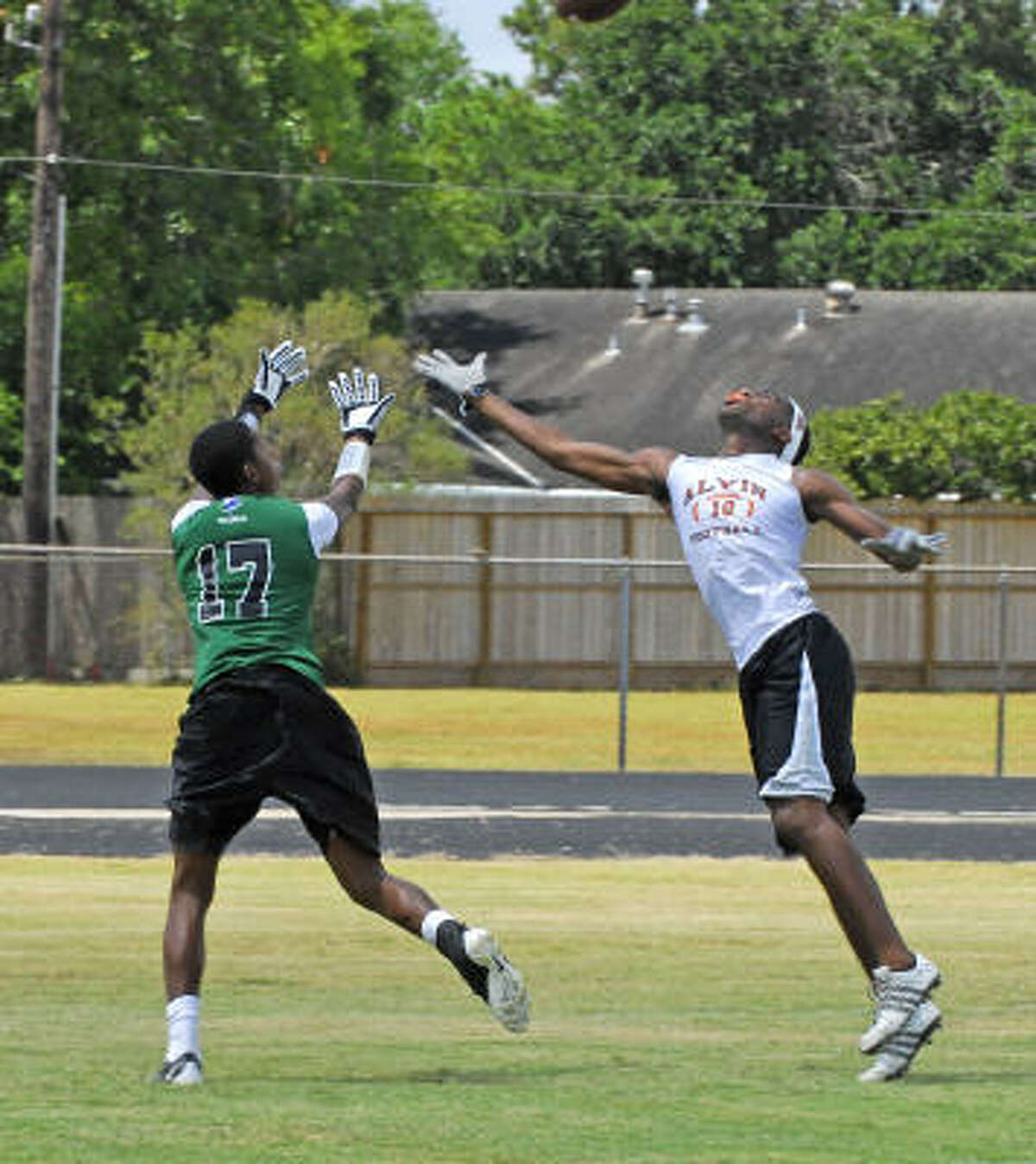 Randall Riggins, No. 17, of Spring reaches for a pass as Bruce Horton of Alvin defends.
