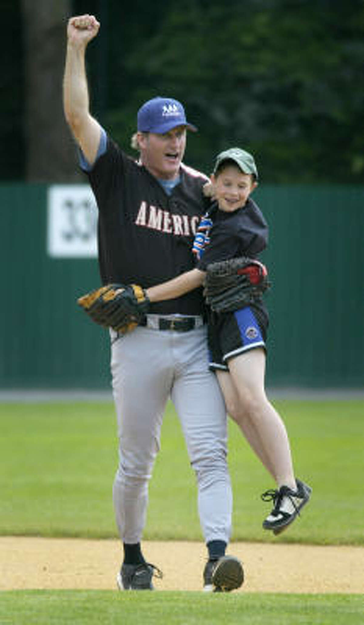 Former major league player Steve Lyons picks up 11-year-old Zachary D'Errico after D'Errico made a double play during the Baseball Hall of Fame Classic.