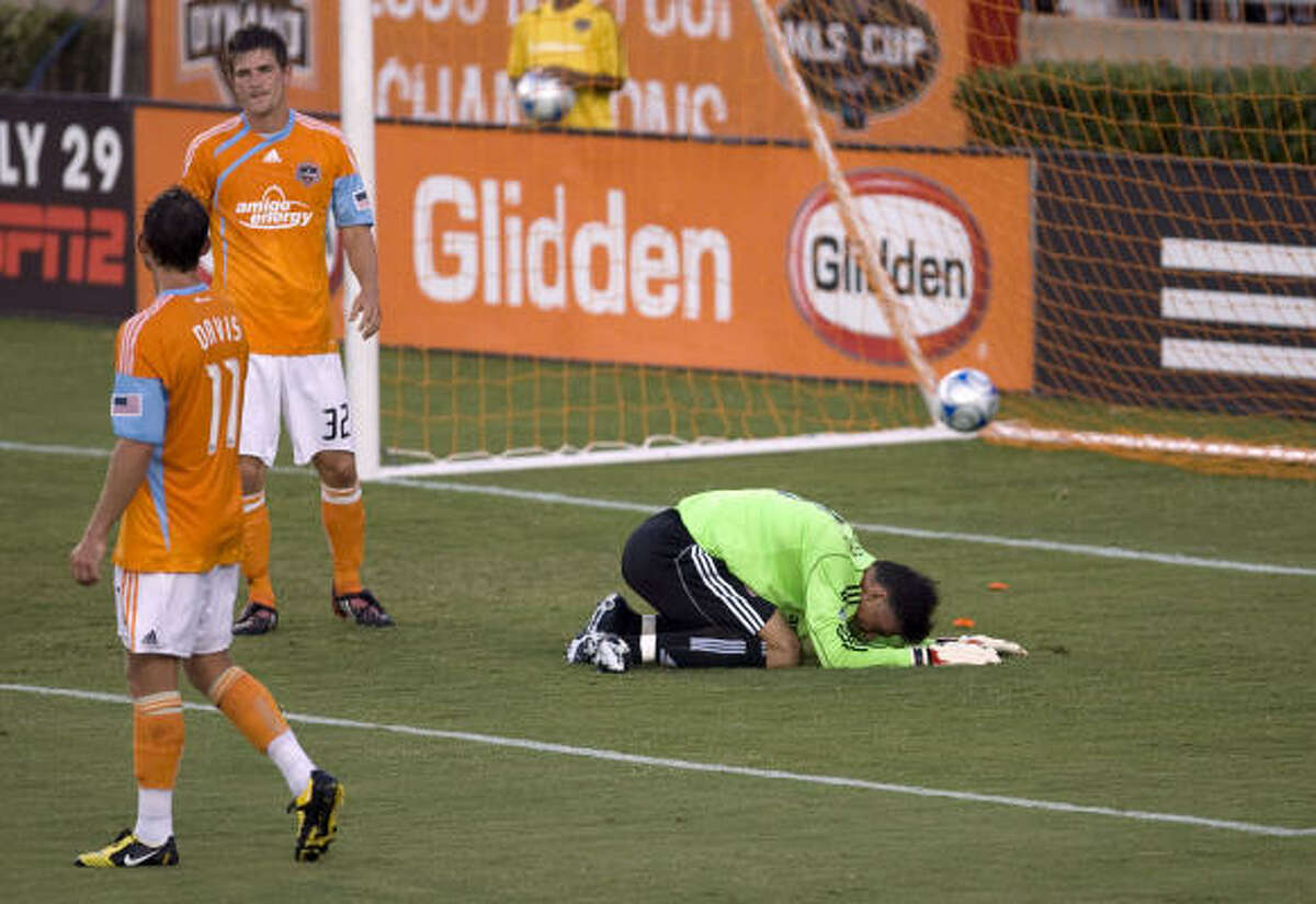 The Houston Dynamo's goalkeeper Pat Onstad (right) reacts after a goal is scored against him as teammates Brad Davis (left) and Bobby Boswell (center) look on.