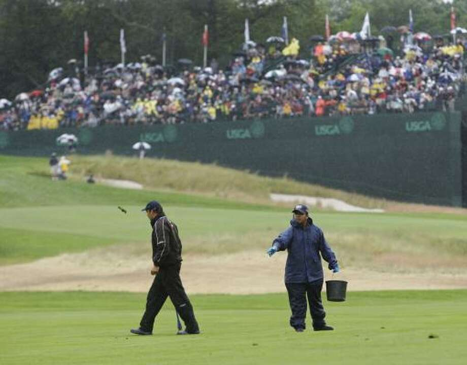 Course workers repair divets on the first fairway before the third round of the U.S. Open. Photo: Mike Groll, AP