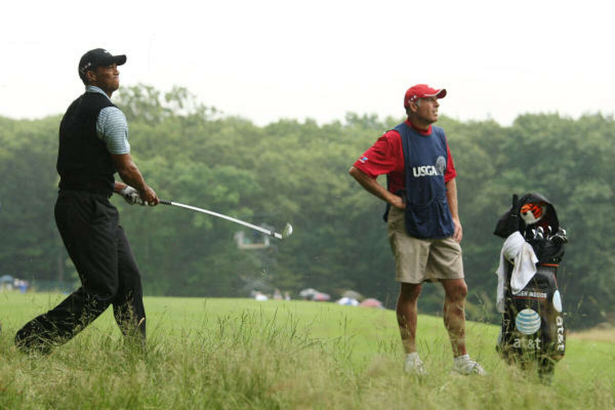 Tiger Woods plays a shot from the rough on the ninth hole.