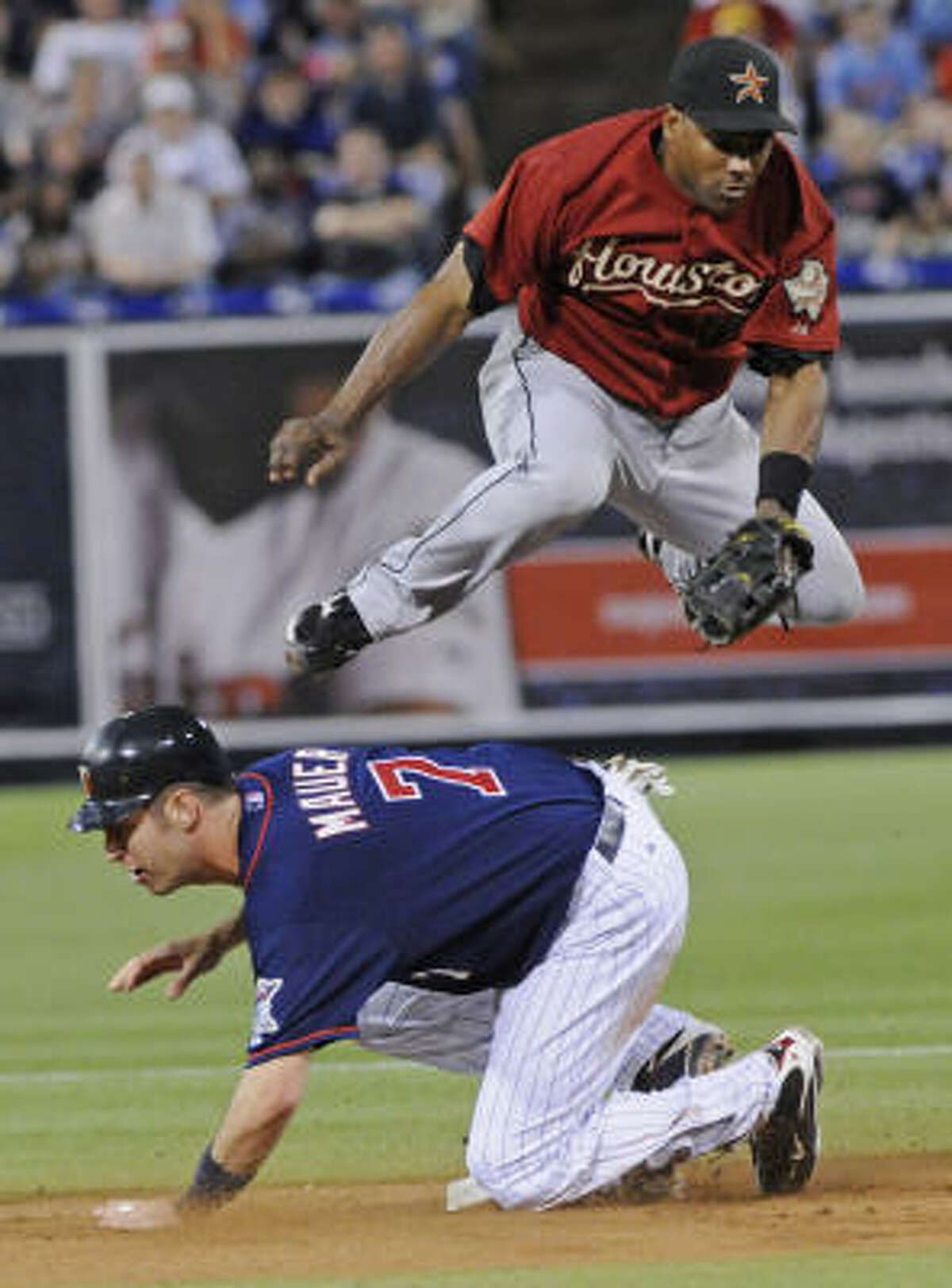 Houston Astros shortstop Miguel Tejada, top, leaps over Minnesota Twins' Joe Mauer at second after completing the double play in the first inning.