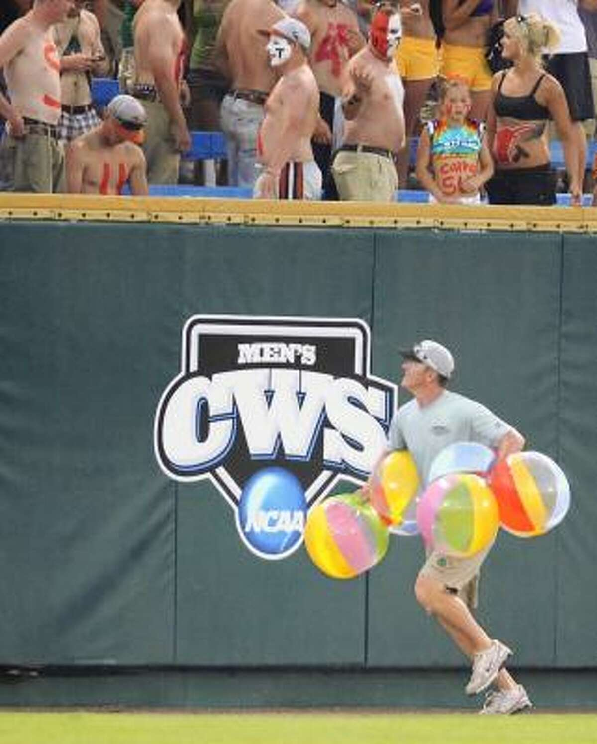 A member of Rosenblatt Stadium grounds crew collects beach balls that fell onto the field while ASU took on Texas in Omaha, Neb.