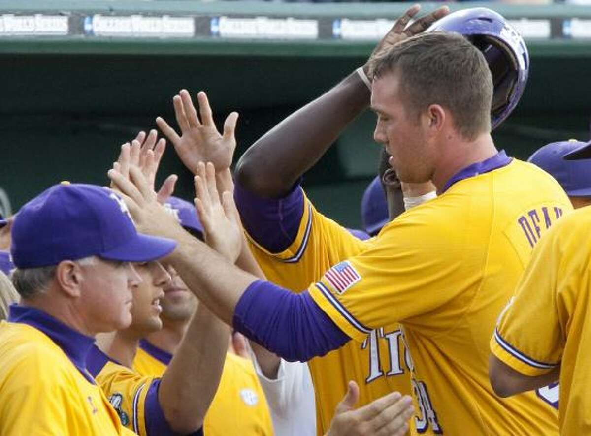 Day 1: LSU 9, Virginia 5 LSU's Blake Dean, right, is greeted at the dugout by teammates after scoring against Virginia on a single by Micah Gibbs in the first inning.