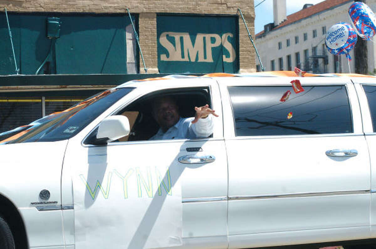 A Juneteenth parade participant throws candy out the window.