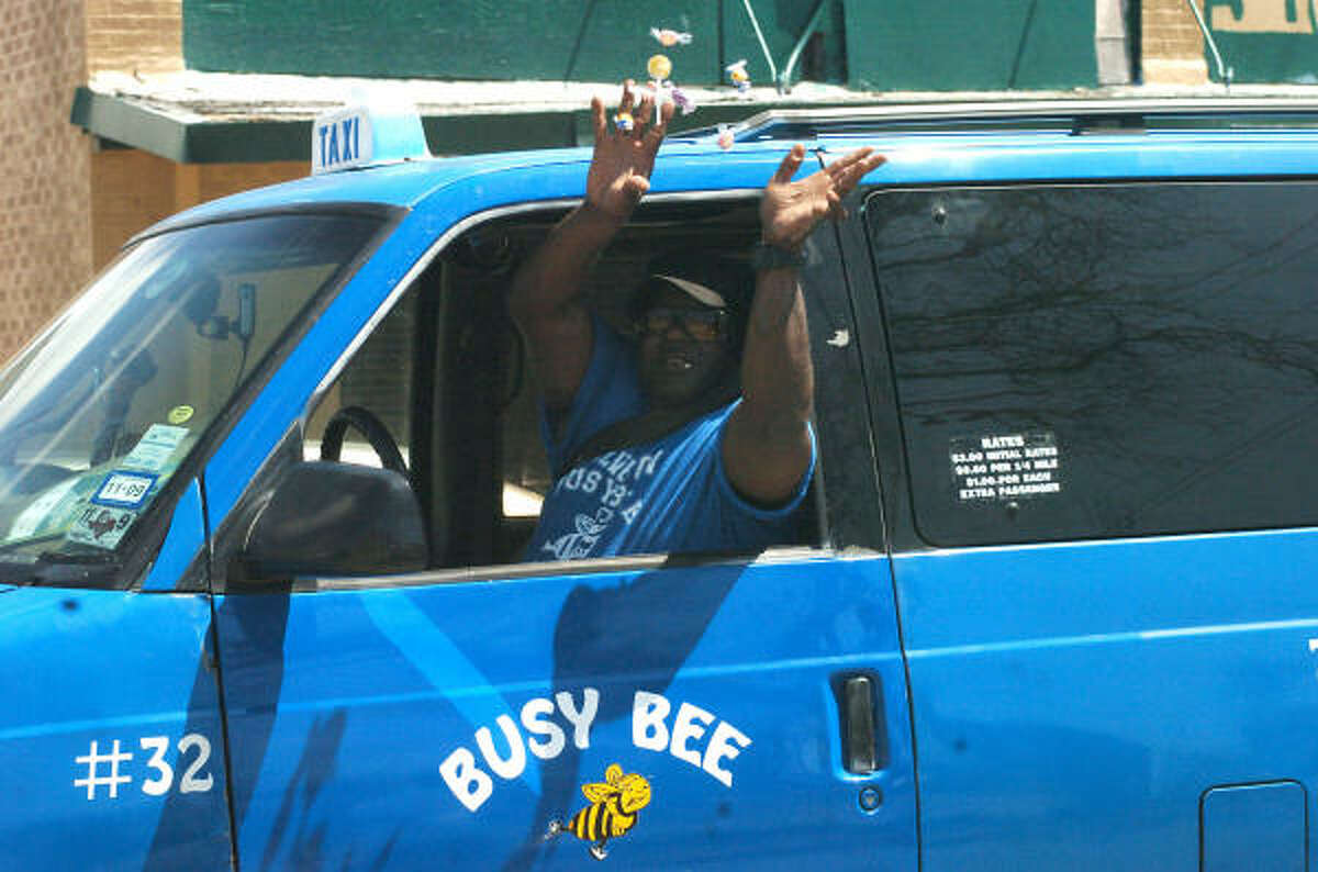 A taxi driver throws candy to parade goers.