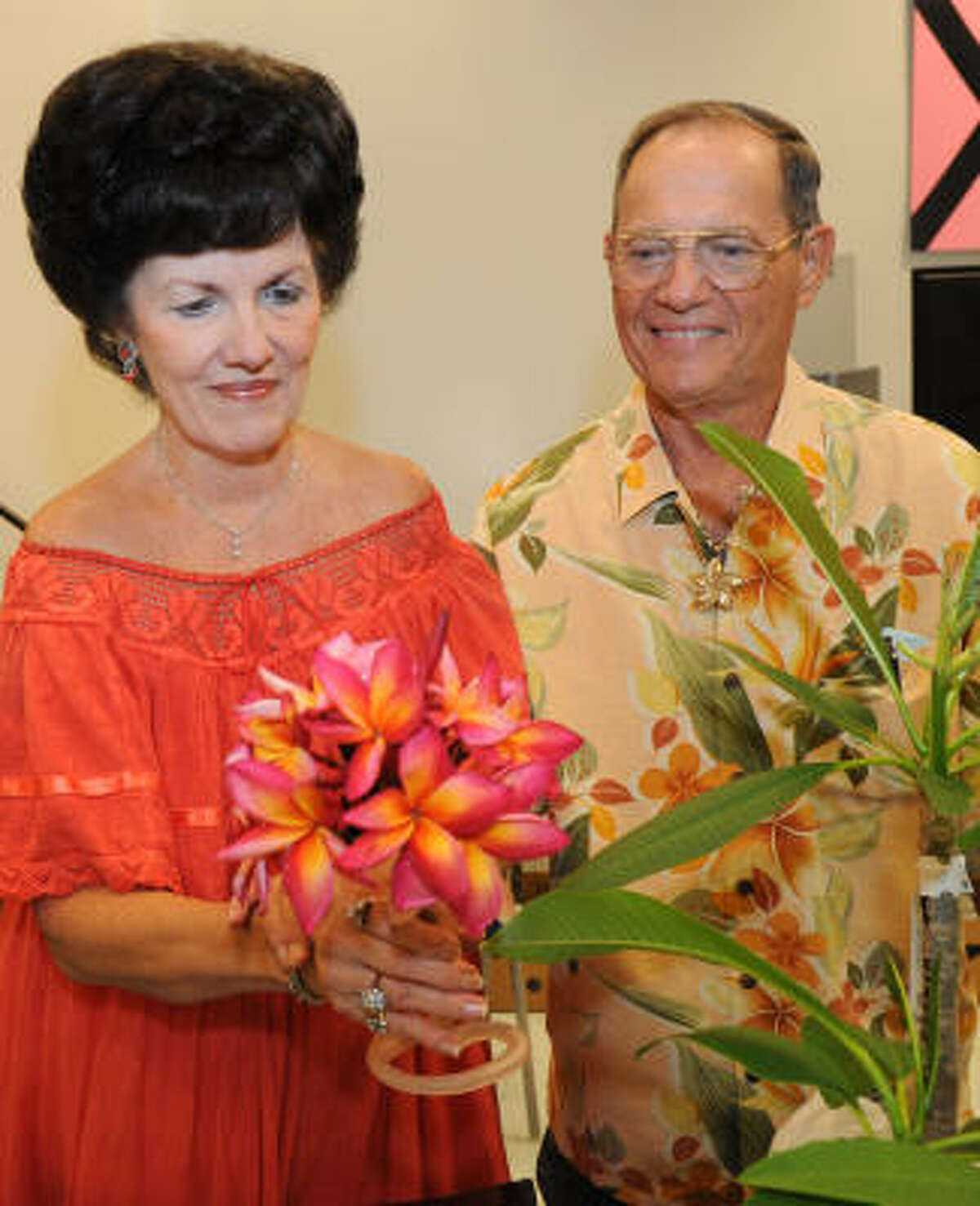 Nancy Wills shows off a plumeria variety called Jeannie Morgane. Her husband, Emerson, accompanied her.