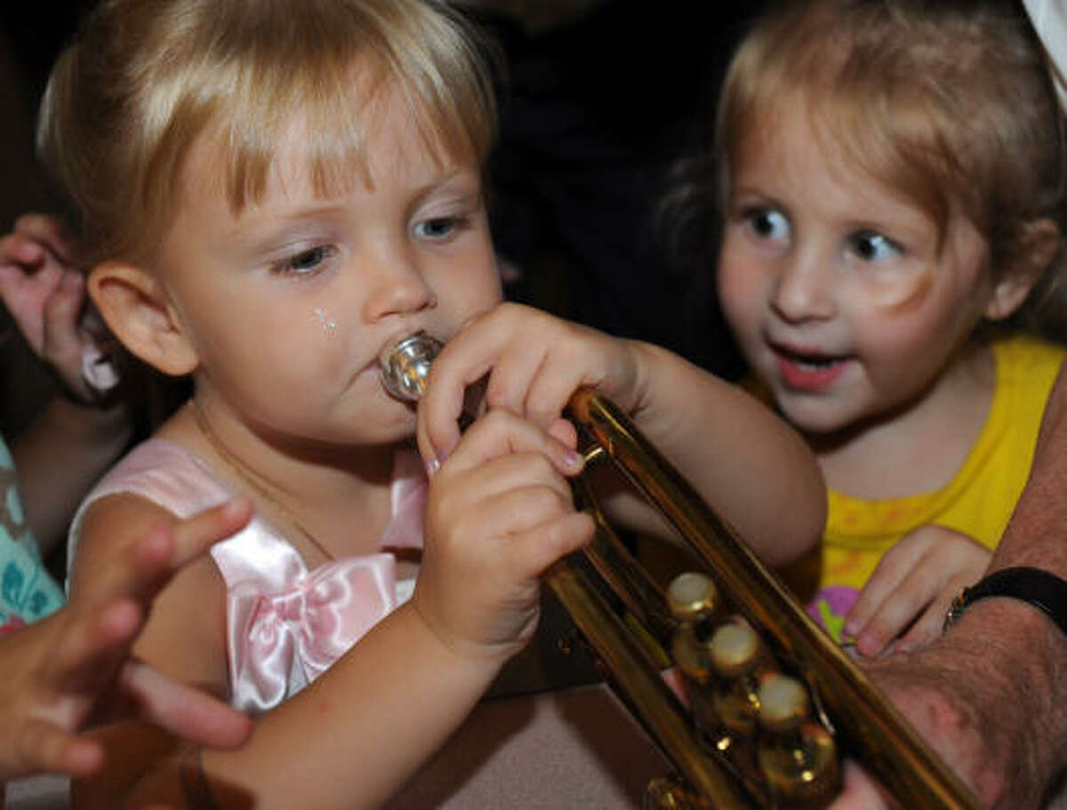 Shelley Stovall, 3, impresses cousin Becca Stovall, also 3, with her trumpet debut at the Houston Symphony's instrumental petting zoo before the June 13 concert.