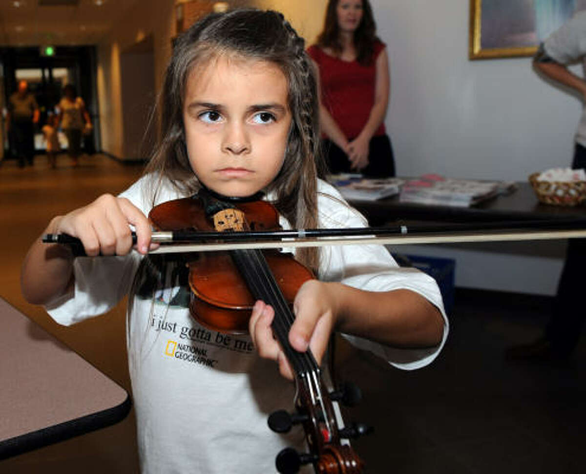 Katy May Hergerty, 6, tries out a violin before the Sounds Like Fun concert.