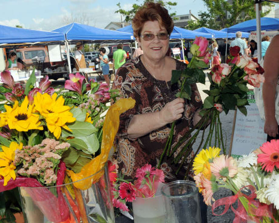 Debbee Cooks explores the flowers at the Farmers Market at Clear Lake Shores. Photo: Kim Christensen, For The Chronicle