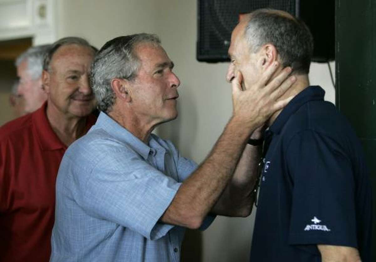 Rangers team owner Thomas Hicks, left rear, looks on as former president George W. Bush, center, jokes around with Rangers radio announcer Eric Nadel, right, who recently underwent retina surgery, during a pregame ceremony. The owner's suite at the ballpark was renamed in honor of the former president.