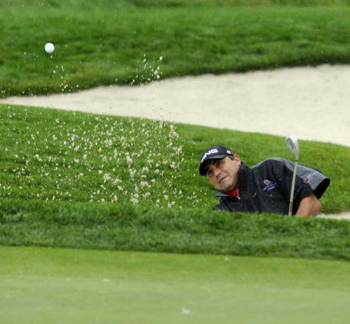 Angel Cabrera of Argentina, the 2009 Masters champion, plays from the sand during the first round.