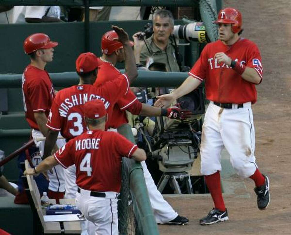 The Rangers' Ian Kinsler, right, is congratulated by teammates and staff after stealing third and then scoring on a throwing error by Astros catcher Ivan Rodriguez in the first inning.