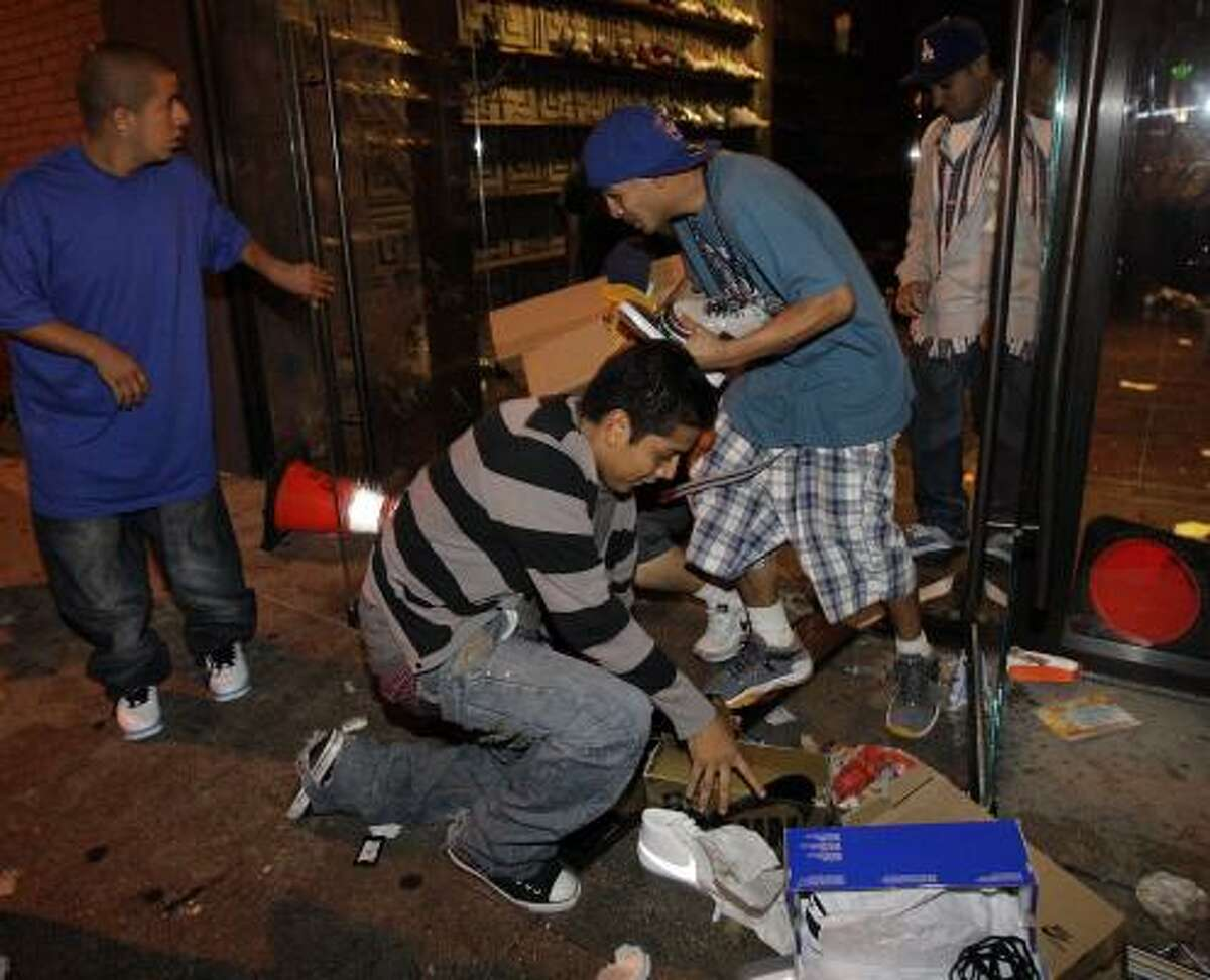 A group of people take goods from a shoe store in downtown Los Angeles after the Lakers' victory.