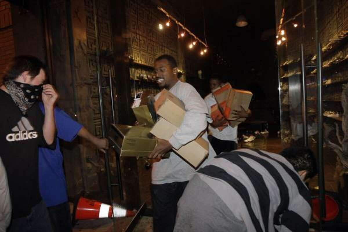 A group of people take goods from a shoe store in downtown Los Angeles on Sunday, after the Lakers defeated the Orlando Magic to win the NBA title.
