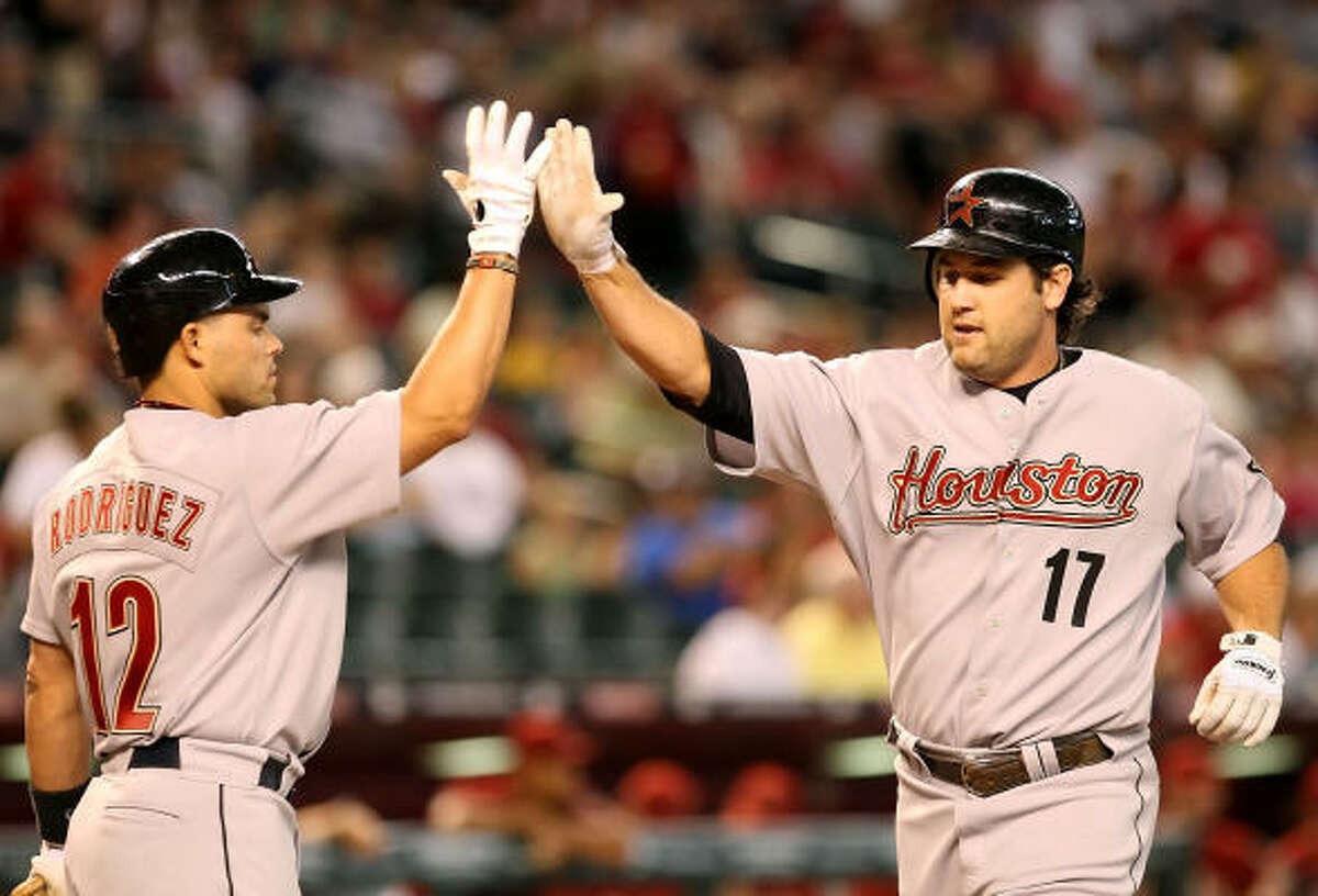 Lance Berkman, right, is congratulated by Ivan Rodriguez after hitting a two-run homer in the first inning, the 301st of his career.