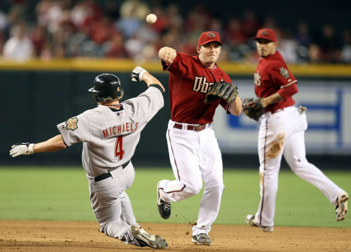 Arizona infielder Stephen Drew throws over Jason Michaels to complete a double play during the sixth inning.