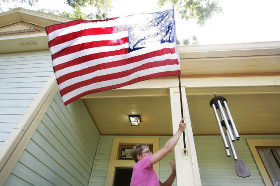 Jennifer Kirk places the flag in front of her home in the Houston Heights. (The family was reminded of the holiday during a church service, then decided to put one out afterward.) Photo: Mayra Beltran, Chronicle