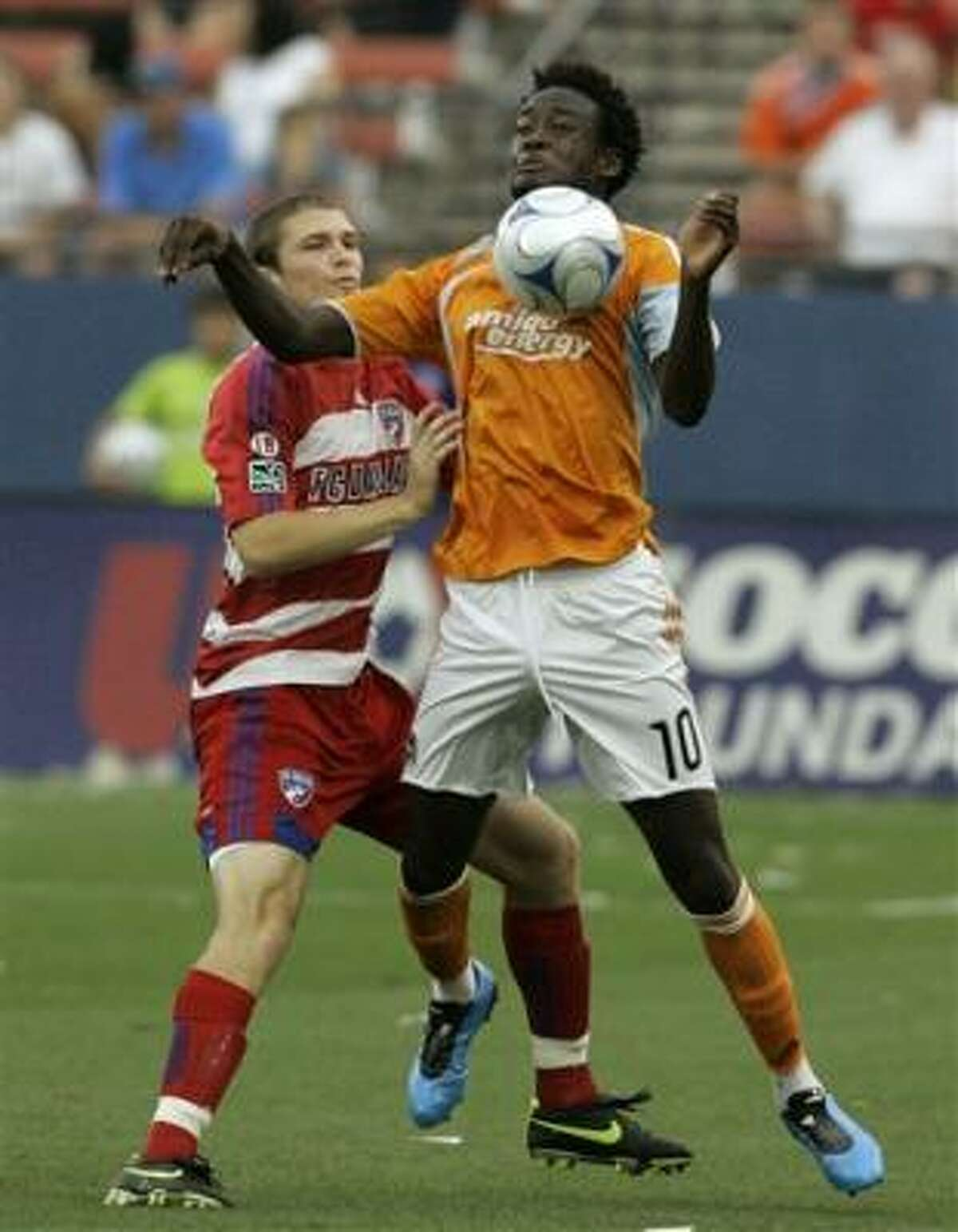 Houston's Kei Kamara, 10, attempts to control the ball in front of FC Dallas defenseman Kyle Davies, left, in the first half of a MLS soccer game in Frisco on Saturday.