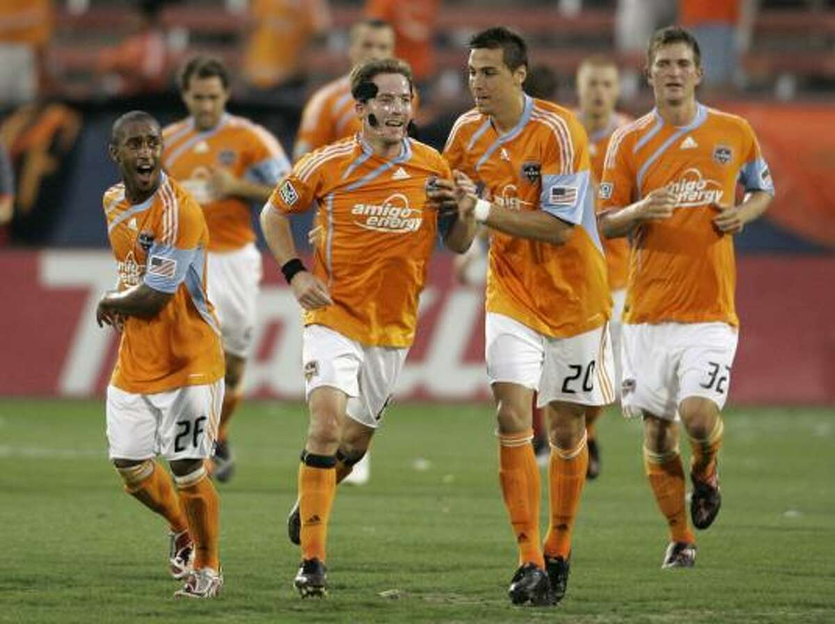 Houston's Corey Ashe (26), Geoff Cameron (20) and Bobby Boswell (32) celebrate with Richard Mulrooney, second from left, following Mulrooney's goal against FC Dallas in the first half Saturday.